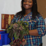 WVC intern Destiny James prepares vegetables for customers.