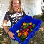 Liv Charlton shows off the fruits of her labor with this tub of USDA organic peppers.